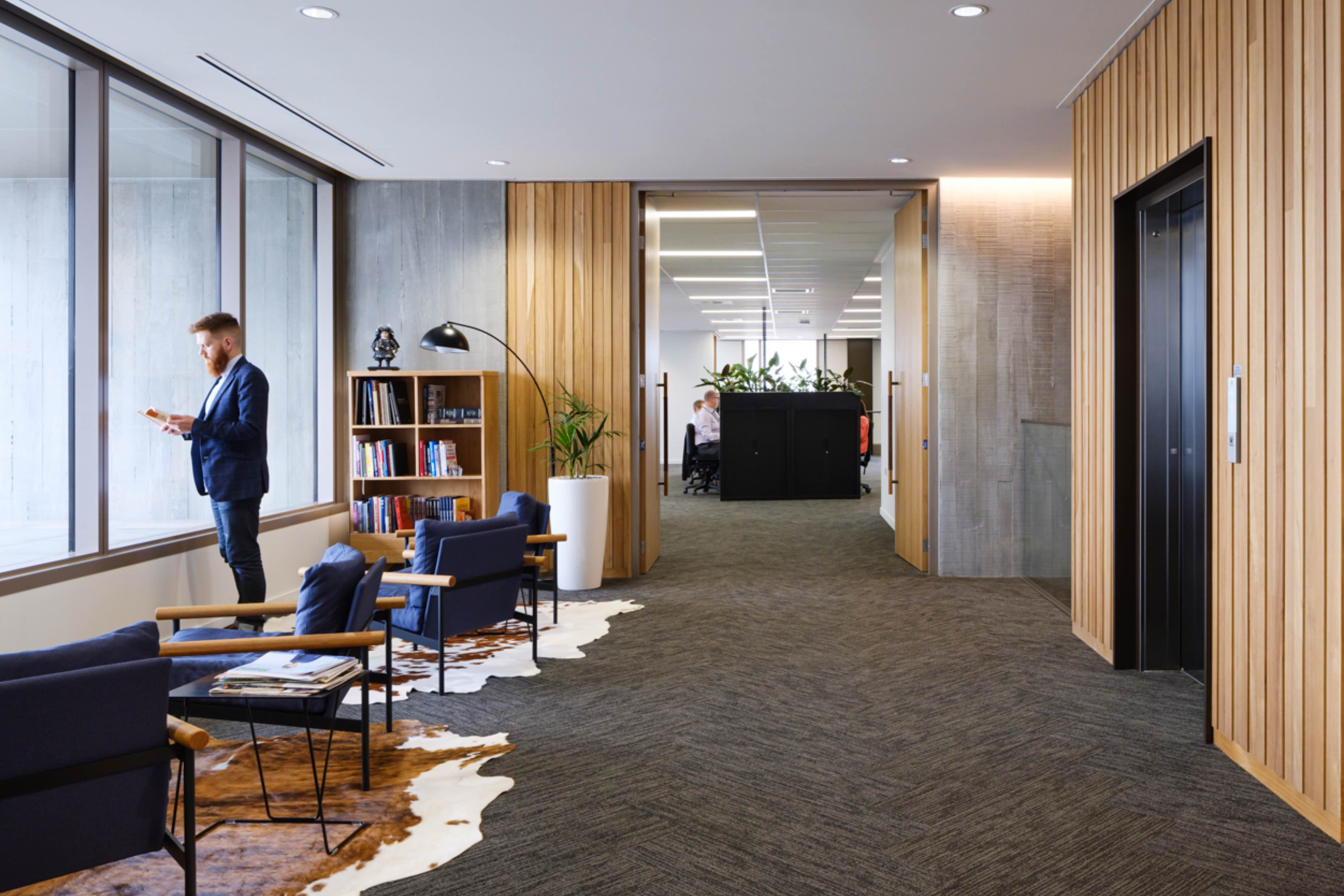 Suited man in waiting area with contemporary office space visible through open doorway